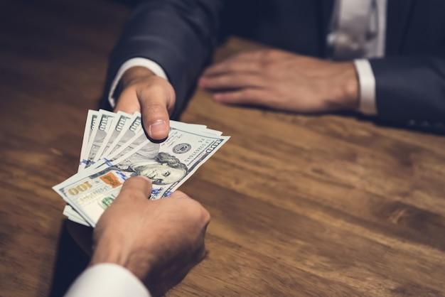 Empresario dando dinero a su compañero en la mesa en la oscuridad