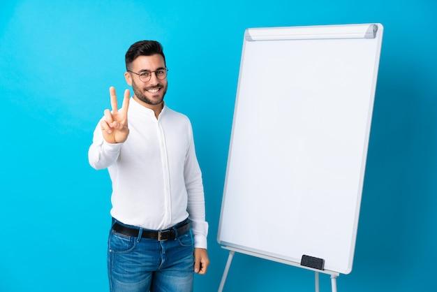 Empresario dando una presentación en pizarra dando una presentación en pizarra y mostrando el signo de la victoria