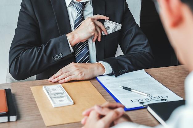 Empresario dando sobornos de corrupción de billetes de dólar al gerente de negocios