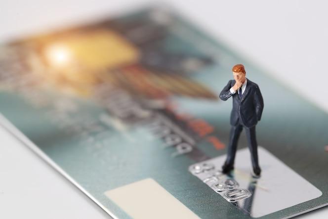 Empresario de pie y pensando en tarjeta de crédito como solución en línea de pago y compra