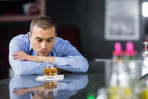 Empresario deprimido mirando vasos de whisky