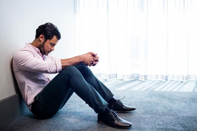 Empresario deprimido sentado contra una pared y mirando hacia abajo