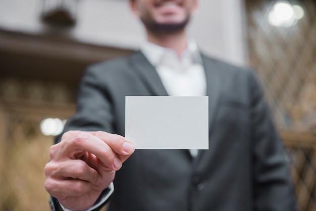 Empresario desenfocado mostrando tarjeta de visita blanca