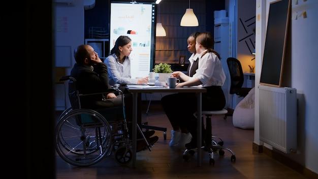 El empresario discapacitado con exceso de trabajo en silla de ruedas se ignora mientras trabaja en la sala de reuniones de la oficina de negocios de la empresa a altas horas de la noche