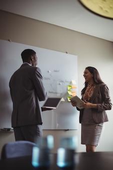 Empresario discutiendo sobre pizarra blanca con un colega