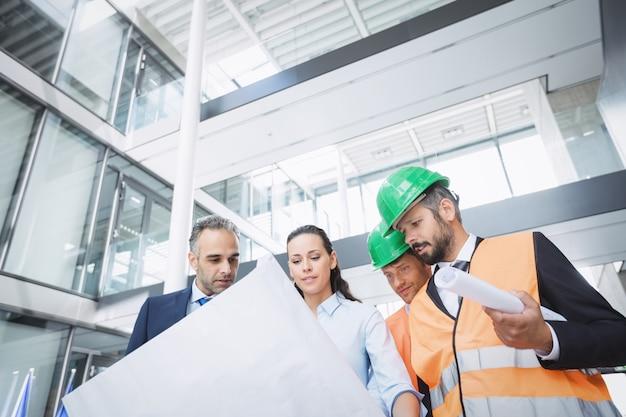 Empresario discutiendo sobre planos con arquitectos