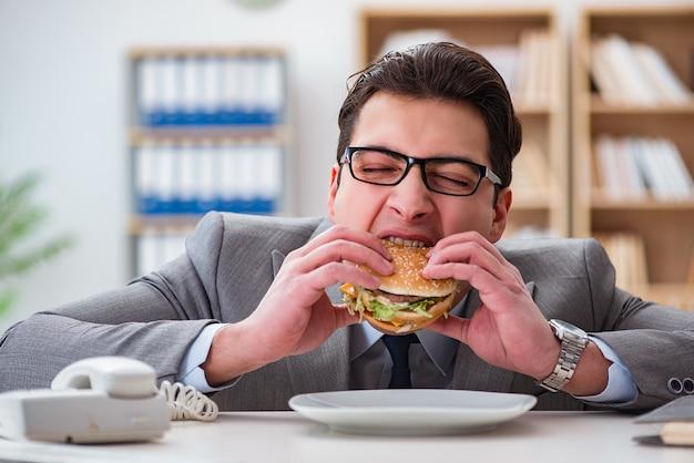 Empresario divertido hambriento comiendo sandwich de comida chatarra