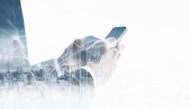 Empresario de doble exposición usando teléfono móvil inteligente