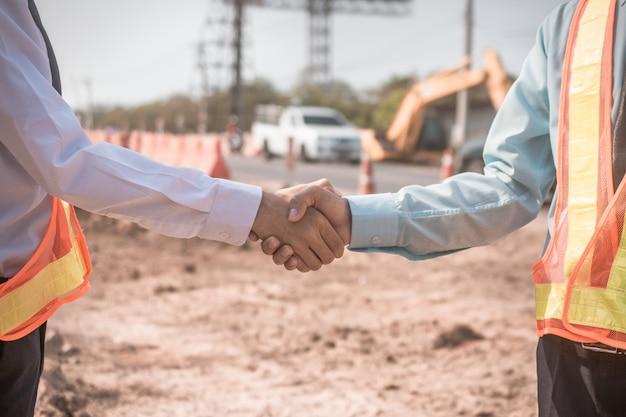 El empresario dos personas estrechan la mano del éxito en la comunidad de asociación del sitio de construcción