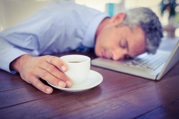 Empresario durmiendo en la computadora portátil y tocar la taza de café