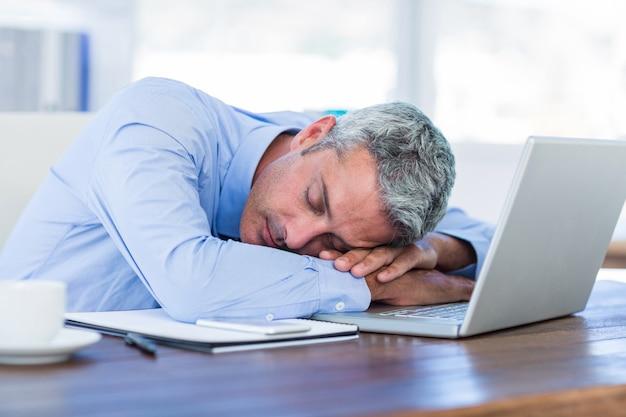 Empresario durmiendo en la computadora portátil