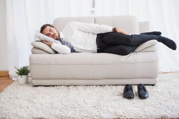 Empresario durmiendo en el sofá después de un largo día