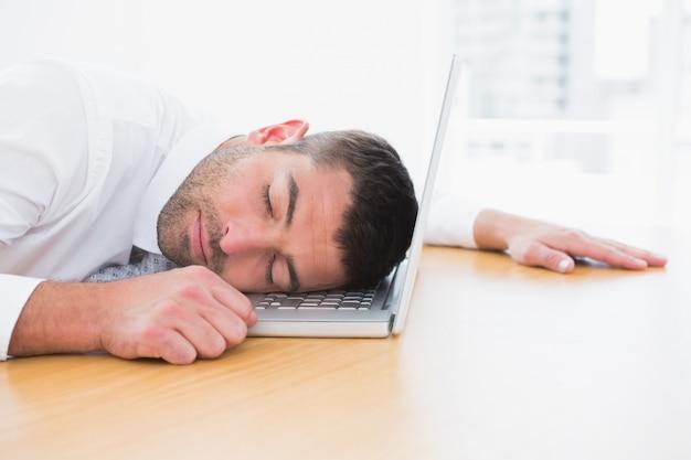Empresario durmiendo en su computadora