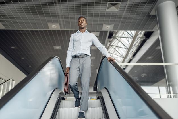 Empresario de ébano con maletín descendiendo por la escalera mecánica en el centro comercial. persona de negocios exitosa, hombre negro en ropa formal, centro comercial
