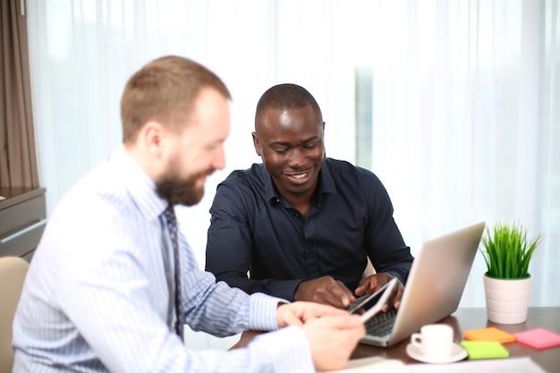Empresario de edad sonriente mirando a un colega en la reunión del equipo, líder del equipo atento feliz escuchando la nueva idea del proyecto, mentor de entrenador