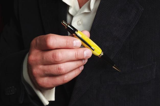 Empresario en elegante traje tiene una pluma en sus manos