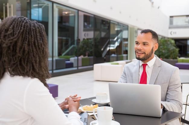 Empresario emocionado positivo chateando con compañero de trabajo
