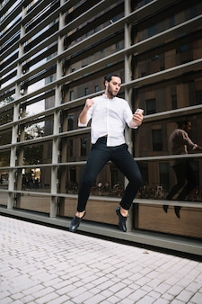 Empresario emocionado saltando en el aire con alegría mirando el teléfono móvil