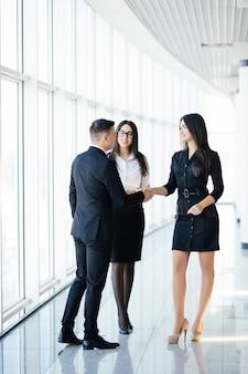 Empresario y empresaria de cuerpo completo un apretón de manos en la sala de la oficina en una reunión informal