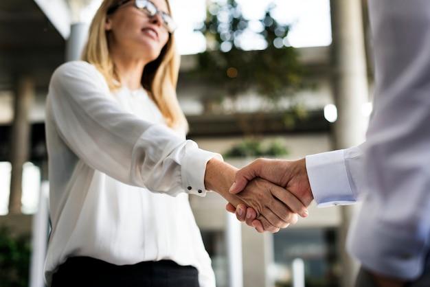 Un empresario y una empresaria dándose la mano en acuerdo.