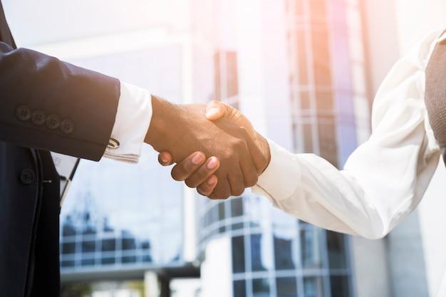 Empresario y empresaria dándose la mano delante del edificio corporativo