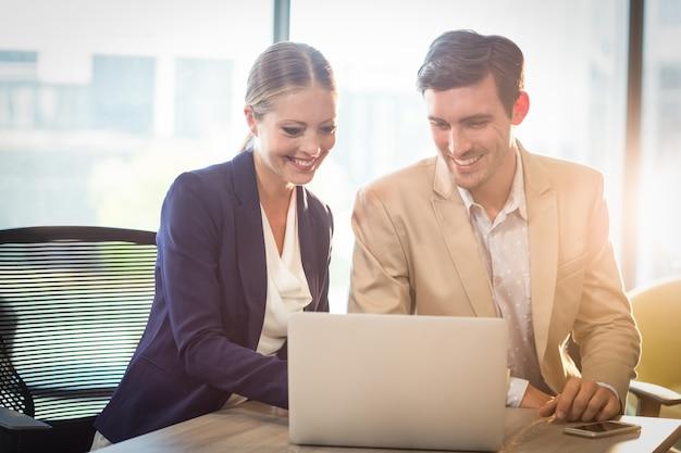 Empresario y empresaria interactuando usando laptop