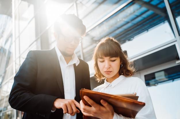 Empresario y empresaria miran documentos importantes