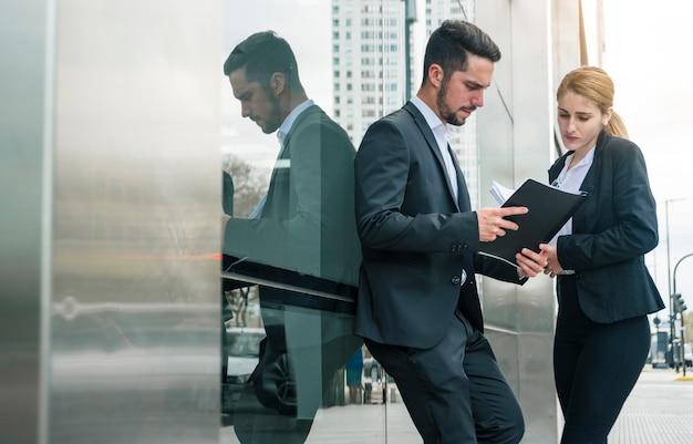 Empresario y empresaria mirando documentos de pie fuera de la oficina