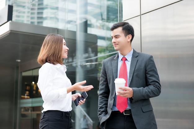 Empresario y empresaria de pie y charlando fuera del edificio de oficinas