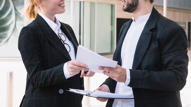 Empresario y empresaria sosteniendo documentos en manos