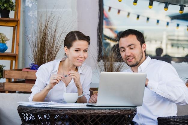 Empresario y empresaria trabajando al aire libre en street cafe durante el almuerzo