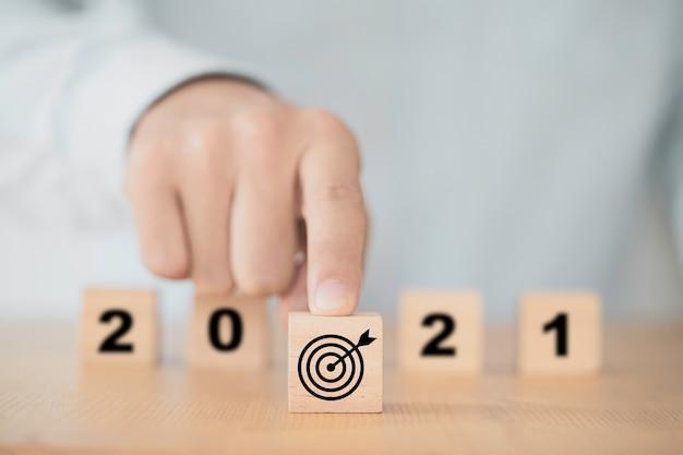 Empresario empujando la placa de destino en el frente del año 2021 para comenzar el plan de negocios de año nuevo.