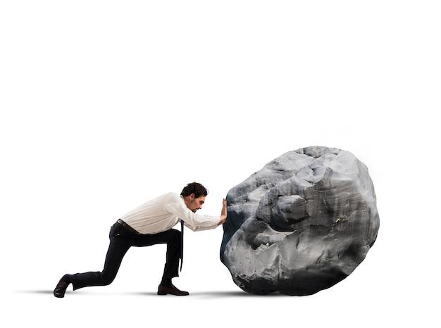 Empresario empujando una roca pesada con gran esfuerzo