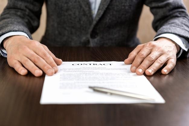 El empresario entrega un contrato de firma ofreciendo un bolígrafo. cálido resplandor de la luz del sol.