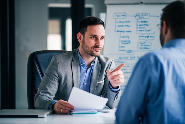 Empresario entrevistando a solicitante de trabajo en la oficina.