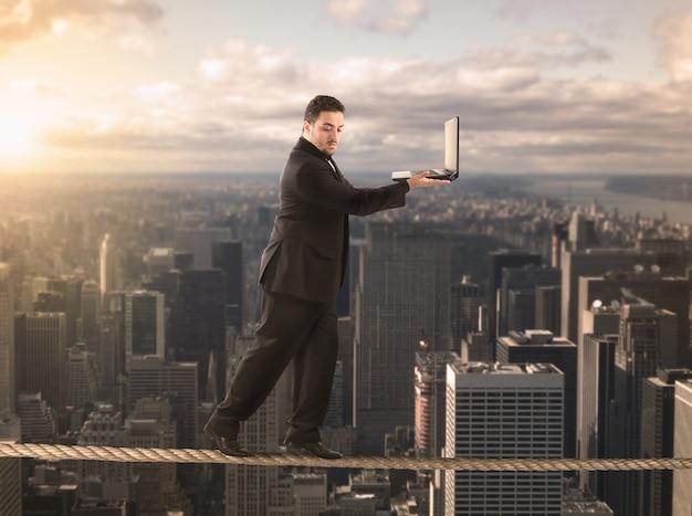 El empresario está en equilibrio sobre una cuerda y sostiene una computadora portátil