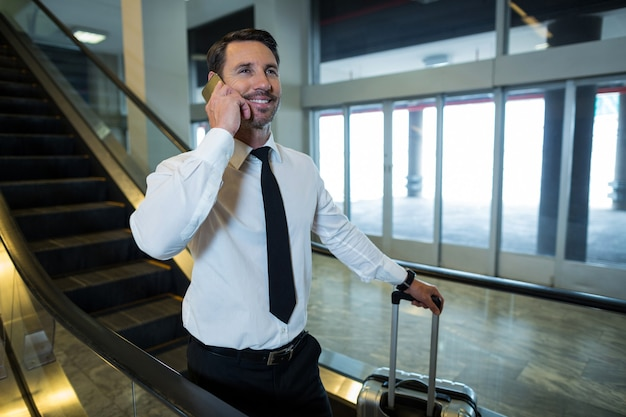 Empresario en escalera mecánica hablando por teléfono móvil