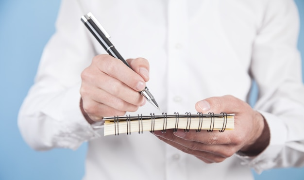 Empresario escribiendo en un bloc de notas en la oficina.