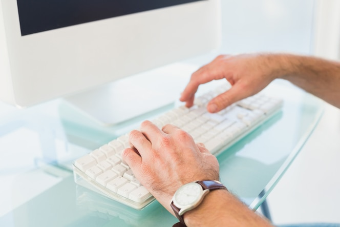 Empresario escribiendo en el teclado de la computadora en su oficina