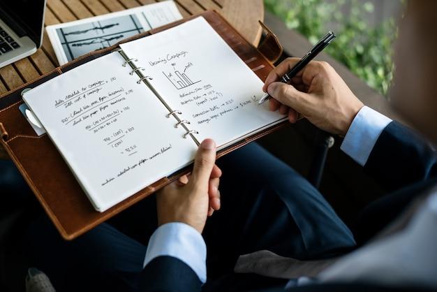Empresario escribiendo un plan de negocios en un cuaderno