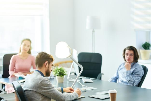 Empresario escribiendo tareas en reunión de personal