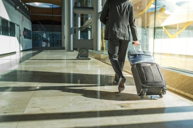 Empresario espalda y piernas caminando con equipaje en el aeropuerto