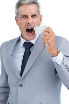 Empresario estafando la cinta adhesiva de la boca