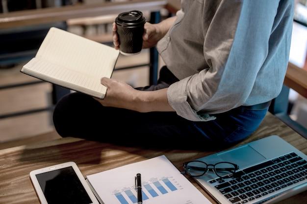 Empresario en estilo casual trabajando sentado en el borde de la mesa
