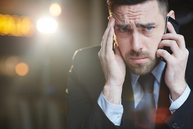 Empresario estresado haciendo llamada telefónica