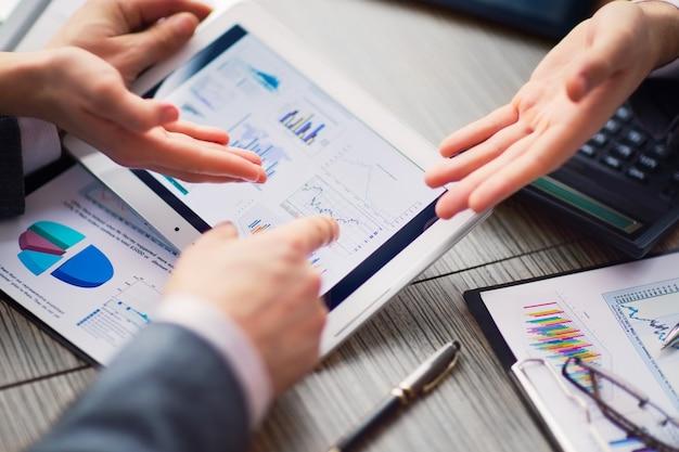Empresario de evaluación financiera en línea en una tableta. trabajo en equipo en la oficina