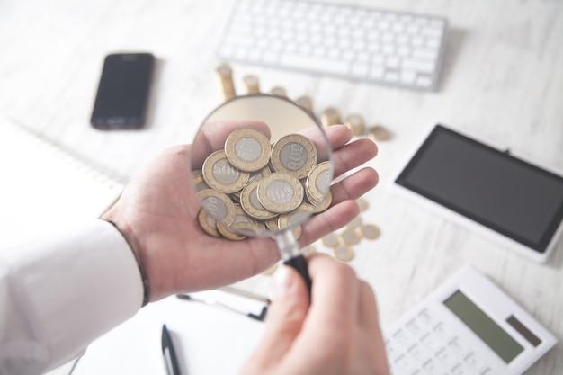 El empresario examina las monedas a través de una lupa.