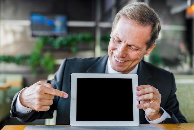 Empresario feliz apuntando a la pantalla en blanco de la tableta digital