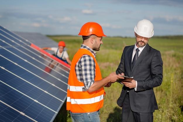 Empresario firma contrato con capataz, técnico examina paneles solares