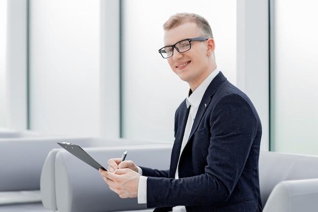 El empresario firma un documento comercial sentado en el vestíbulo de la oficina